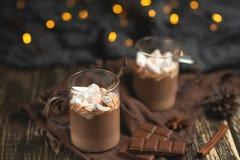 Gorąca czekolada z cynamonowymi kijami, anyżem, dokrętkami i kakaowym proszkiem na, nieociosanych drewnianych tła, czekoladowych  fotografia stock