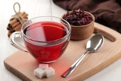 Gorąca czerwona karkade herbata w szklanych filiżankach z suchą herbatą na białym drewnianym stole zdjęcie stock