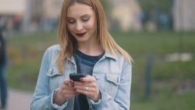 Gorąca delikatna blondynka komunikuje przez smartphone z rewolucjonistek warg dziewczyny inblue drelichu dworskim i surowym bluse zbiory wideo