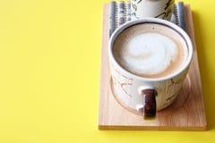 Gorąca filiżanka cappuccino kawa na koloru żółtego stołu tle fotografia royalty free