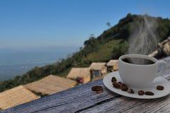 Gorąca filiżanka i kawowe fasole na drewnianym stole z zwiedzającym tłem Fotografia Stock