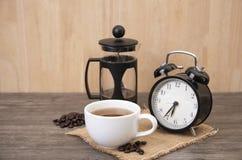Gorąca filiżanka kawy i budzik na drewnie Obraz Stock