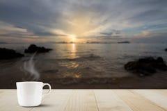Gorąca filiżanka na drewnianym stołowym wierzchołku na zamazanym złotym nieba, morza i wyspy tle podczas wschodu słońca, Zdjęcie Stock