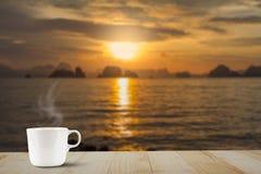 Gorąca filiżanka z kontrparą na drewnianym stołowym wierzchołku na zamazanym złotym nieba, morza i wyspy tle, Zdjęcia Royalty Free