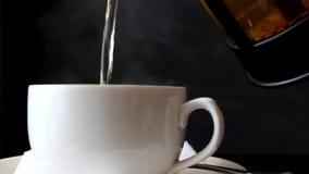 Gorąca herbata nalewają w filiżankę od teapot zdjęcie wideo