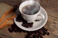 Gorąca herbata w białej filiżance z kawowymi fasolami i plasterka chlebem Zdjęcia Stock