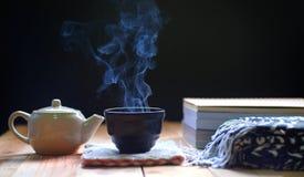 Gorąca herbata w teapot i filiżance na drewno stole, fotografia stock