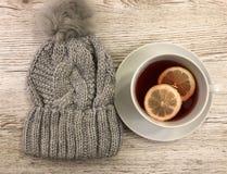 Gorąca herbata z cytryną i czapeczką ciepłą, milutką, fotografia royalty free