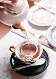 Gorąca Jabłczana herbata słuzyć nalewać od kubka przez stal nierdzewna durszlaka herbacianego infuser w porcelana rocznika filiża fotografia royalty free