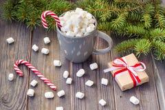 Gorąca kawowa czekolada z marshmallow na nieociosanym drewnianym stołowym tle, cukierek trzcin prezenta pudełek jedlinowy drzewo Zdjęcie Stock