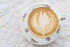 Gorąca Latte sztuki kawa w rocznik filiżance na stole Zdjęcie Stock