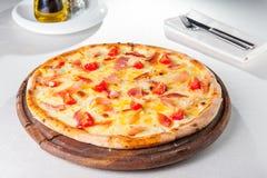 gorąca mięsna pizza z hamon, serem i czereśniowymi pomidorami na drewnianej desce na słuzyć restauracja stole, Obrazy Stock