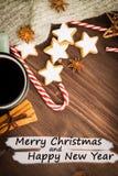 Gorąca parująca filiżanka glint wino z pikantność, anyż, cynamon, ciastka w kształcie gwiazda, czerwoni cukierki, pieprz na drewn zdjęcie stock