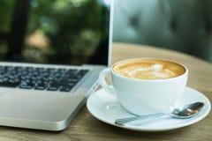 Gorąca sztuki Latte kawa w filiżance na drewnianym stole wewnątrz i laptopie i Fotografia Royalty Free