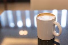 Gorąca sztuki Latte kawa w filiżance na stole Zdjęcia Stock