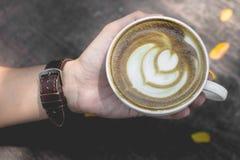 Gorąca zielonej herbaty latte sztuka na drewnianym na ręce Obrazy Stock