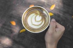 Gorąca zielonej herbaty latte sztuka na drewnianym na ręce Zdjęcie Stock