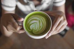 Gorąca zielonej herbaty latte sztuka na ręce na stołowym kawiarnia sklepie Zdjęcie Stock