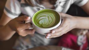 Gorąca zielonej herbaty latte sztuki o ręka na stołowym kawiarnia sklepie Obrazy Royalty Free