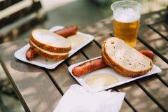 Gorące kiełbasy z chlebem, musztardą i piwem na drewnianym stole, zdjęcie royalty free