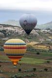 Gorące powietrze balony latają nad krajobrazem blisko Goreme w Cappadocia regionie Turcja Fotografia Stock