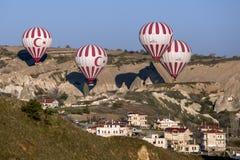 Gorące powietrze balony latają nad wioską przy wschodem słońca blisko Goreme w Cappadocia regionie Turcja Zdjęcie Royalty Free