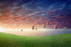Gorące powietrze balony latają w rozjarzonego zmierzchu nieba above zielonej łące obraz stock