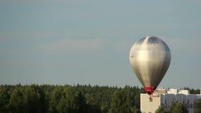 Gorącego powietrza balonowy latanie w niebie nad domami i lasem zbiory wideo