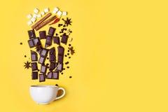 Gorącej czekolady filiżanka, czekoladowi kawałki, pikantność i marshmallows na żółtym tle, zdjęcie royalty free