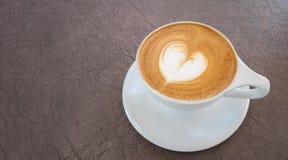 Gorącej kawowej latte sztuki kształta kierowa piana na rzemiennym tle fotografia stock