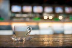 Gorący cappuccino w filiżance na drewnianym stole w cukiernianym plamy tle Fotografia Stock