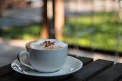 Gorący Cappuccino w filiżance na drewno stole Zdjęcia Royalty Free
