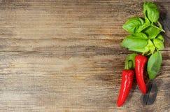 Gorący chili pieprze i basilów liście na drewnie Obrazy Royalty Free