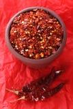 Gorący Czerwoni Chillies miażdżący chili pieprz na czerwieni obraz stock