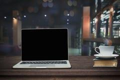 Gorący filiżanka kawy na dużym laptopie na drewno stole w przodzie i książce zdjęcia stock