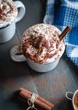 Gorący kakao z batożącym kremowym i cynamonowym kijem na ciemnym tle Odgórny widok obrazy stock