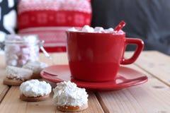 Gorący kakao z marshmallow w czerwonym ceramicznym kubku na drewnianym domu i stole zrobił świeżym piec Bożenarodzeniowym ciastko obraz royalty free