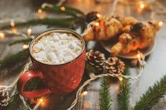 gorący kakao z marshmallows i croissant na nieociosanym drewnianym stole z bożonarodzeniowe światła Zdjęcie Royalty Free