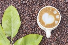 Gorący kawowy kubek na kawowej fasoli i liściach Fotografia Royalty Free