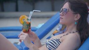 Gorący kurczątko pije świeżego koktajl na plaży, dokucza z jęzorem zdjęcie wideo