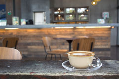 Gorący Latte w filiżance na drewnianym stole w cukiernianym plamy tle Fotografia Royalty Free