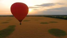 Gorący lotniczy balon unosi się nad polem przy zmierzchem, romantyczna rocznica, miłość zbiory
