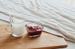 Gorący mleko w szklanej filiżance malinowym dżemu na drewnianej desce i Traktowanie napój lud remedia w łóżku Obraz Stock