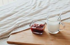 Gorący mleko w szklanej filiżance malinowym dżemu na drewnianej desce i Traktowanie napój lud remedia w łóżku Obrazy Stock