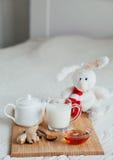 Gorący mleko w szklanym miodzie na drewnianej desce i filiżance Traktowanie dziecko napój lud remedia w łóżku miękka zabawka Obrazy Stock