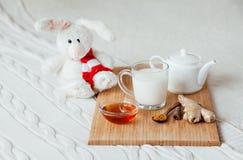 Gorący mleko w szklanym miodzie na drewnianej desce i filiżance Traktowanie dziecko napój lud remedia w łóżku miękka zabawka Zdjęcie Royalty Free