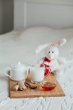 Gorący mleko w szklanym miodzie na drewnianej desce i filiżance Traktowanie dziecko napój lud remedia w łóżku miękka zabawka Zdjęcie Stock