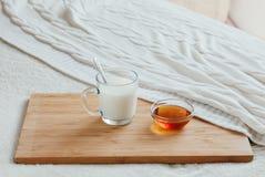 Gorący mleko w szklanym miodzie na drewnianej desce i filiżance Traktowanie napój lud remedia w łóżku Zdjęcie Royalty Free