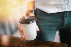 Gorący napój w papierowej filiżance w rękach zamyka up Obraz Stock