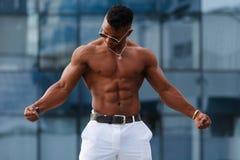 Gorący Piękny czarny facet z wyłupiastymi mięśniami pozuje przeciw tłu miastowy krajobraz Mężczyzna sprawności fizycznej model Fotografia Royalty Free